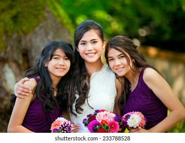 Biracial bride standing with her two bridesmaids outside, smiling and holding flower bouquet