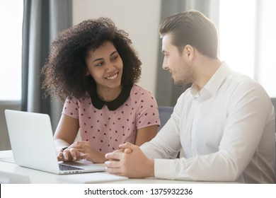 Biracial businesswoman work with businessman people gather in office sitting at desk smile have good teamwork results, diverse colleagues flirting chatting, pleasant conversation at workplace concept