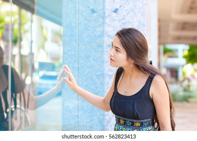Biracial Caucasian Asian teen girl standing in front of large glass window of store, looking in, window shopping