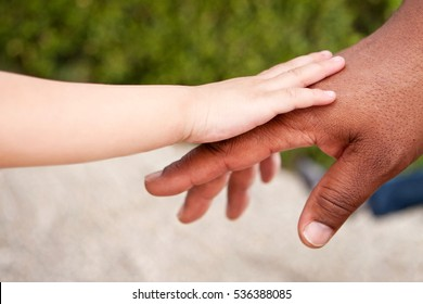 Biracial child holding his fathers hand.