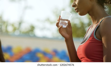 Biracial girl drinking after workout, restoring water balance, hydration