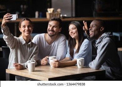 Biracial girl holding in hand phone make selfie photo with friends spend free time with diverse intimates in cafe, generation and modern wireless technology leisure activities in public place concept