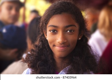 A biracial girl smiling in the crowd.
