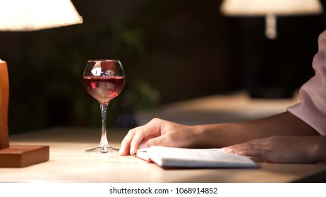 Biracial lady drinking wine and reading her favorite book in cozy restaurant, stock footage