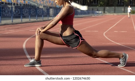 Biracial lady stretching and warming up her leg muscles before starting to run