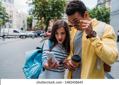 Bi-racial man in sunglasses and woman looking on smartphone and surprising