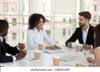 Biracial mixed race team leader presenting new business idea talking to diverse multiracial colleagues company staff during meeting sitting at desk in modern office conference room. Teamwork concept
