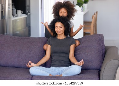 Biracial mother elder sister or babysitter little girl daughter sitting together on sofa in living room at home, do yoga breathing meditating feels good. Stress relief healthy lifestyle habit concept
