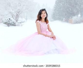 Adolescent de naissance en robe rose solennelle, assise à l'extérieur, dans une belle chute de neige