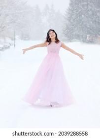 Adolescent oiseau en robe longue et rose en extérieur marchant dans la neige