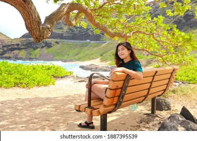 Biracial teen girl relaxing on bench by Hawaiian beach under gnarly shade tree by ocean