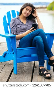 Biracial teen girl sitting on blue adirondack chair beside lake and looking at cellphone