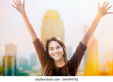 Biracial  teen girl standing with arms raised up, smiling, with morning sunshine hitting skyscrapers and buildings in background