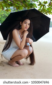 Biracial teen girl or young woman holding black umbrella while sitting on sandy Hawaiian beach in the rain. Sad or lonely expression.