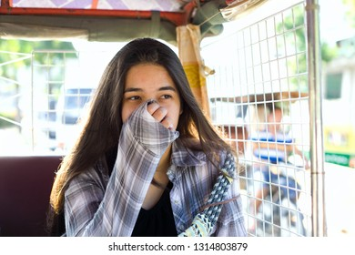 Biracial teen girl or young woman tourist covering nose and mouth from poluution while in tuktuk taxi in Phnom Pehn, Cambodia