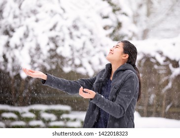biracial teen girl or young woman outdoors in winter enjoying snowfall and trying to catch snowflakes
