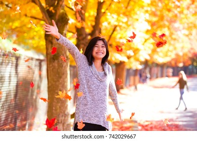 Biracial teen girl or young woman throwing autumn leaves into air, smiling