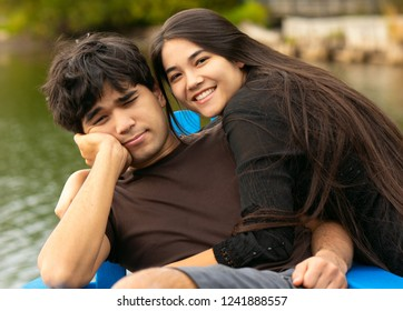 Biracial teen siblings outdoors relaxing in blue adirondack chairs by lake on wooden pier