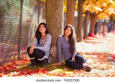 Biracial teen or young woman sitting under colorful maple leaves in autumn, with a carpet of fallen leaves underfoot.