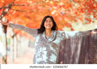 Biracial Thai American teen girl in gray sweater standing under bright red and orange leaf maple tree in autumn with arms outstretched, smiling outdoors