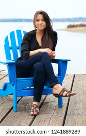Biracial Thai Caucasian teen girl sitting in blue adirondack chair on wooden pier by lake  outdoors