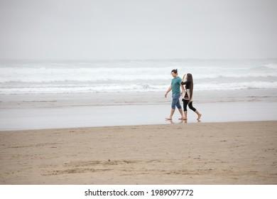 Jeune couple Birman marchant sur une plage vide à côté de l'océan par jour de brouillard