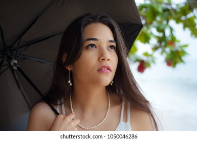 Biracial young woman holding black umbrella while looking up on rainy overcast day on Hawaiian beach.