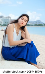 Biracial young woman or teen sitting on beach thinking. Waikiki and Diamond Head in background