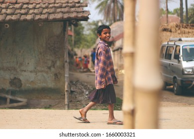 Birbhum, West Bengal/INDIA - February 28 2020: An Indian or asian stranger kid walking on the road and looking at the camera. Happy cheerful face. Bright warm smile. Clay huts,Car visible. Copy space.