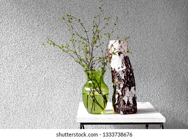 Birch billet and young birch branches in green glass vase against concrete background.