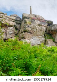 Birchen Edge cliff face with Helsons monument perched on top rises up from dense ferns. HDR, High Dynamic Range, image