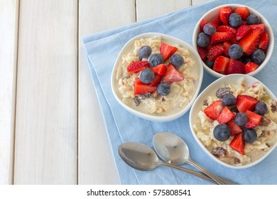 Bircher Muesli with Fresh Berries on White Wooden Table from Above with Copy Space