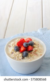 Bircher Muesli with Fresh Strawberries and Blueberries on Top with Copy Space Vertical
