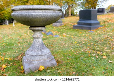 A bird bath on a hill in a cemetery. View is level with the edge of the bath. Graves in the background.
