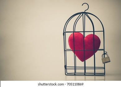 A bird cage with a red heart inside vintage