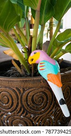 Bird ceramic statue on pot with tree.