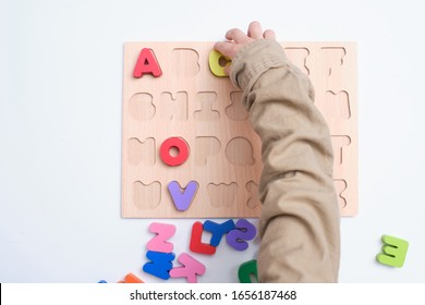 Bird eye view of preschooler, kindergarten boy playing with alphabet blocks, Children learning English with wooden educational abc toy puzzle, Teach young kids English at home, Selective focus