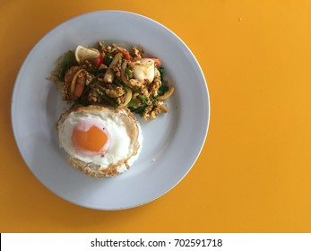 bird eye view of stir fried seafood in curry powder serve with rice and fried egg on white plate on yellow table