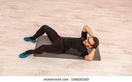 Bird eye view of a young man with spectacles doing sit-ups on the floor in a gym.