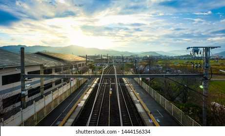 Bird eyes view of train railway at a station in Japan, Sunset scene of locomotive track at countryside background, platform of local trainstation.