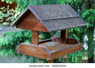 Bird feeder in the form of a house, made of wood and installed in the park.