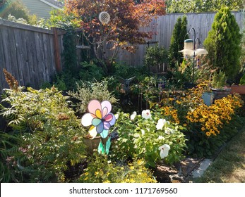 bird feeders, plants, and yellow flowers in backyard with wood fence