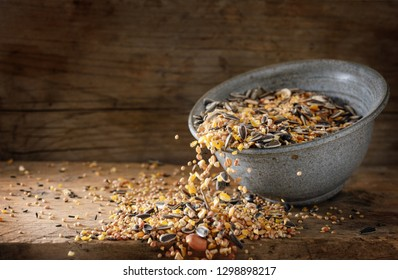 bird food for winter feeding, mixed seeds like sunflower, corn, millet and more are falling out of a bowl on a rustic wooden board, copy space, motion blur, selected focus, narrow depth of field