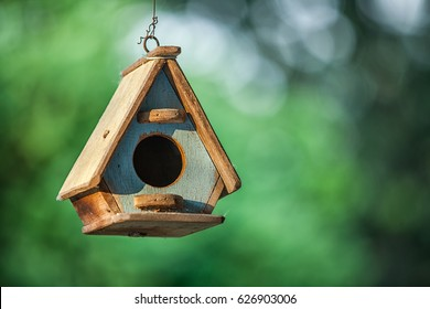 A bird house or bird box in natural green leaves background