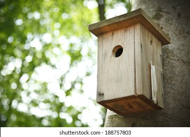 Bird house hanging from the tree with the entrance hole in the shape of a circle.