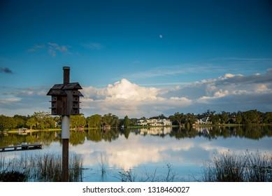 Bird house on lake at sunset