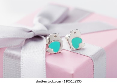 Bird shape with turquoise heart earring studs on pink gift box with bow as background. Cute jewelry for child girl. Present for birthday