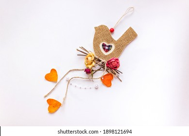 Bird shaped decorative element on a white background. Textile toy made of sackcloth in form of bird sitting on dry branches and roses with pearl beads and mandarin peel hearts. Concept sublime love.