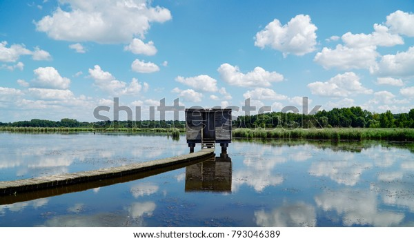 Bird spotting shed on the lake with clouds reflected on the water surface