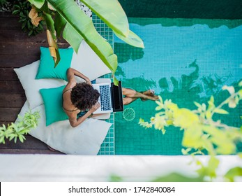bird view of a remote online working digital nomad women with curly hair and laptop sitting at a sunny turquoise water pool surrounded by cushions and plants in the foreground